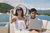 Couple Using Laptop Aboard Yacht